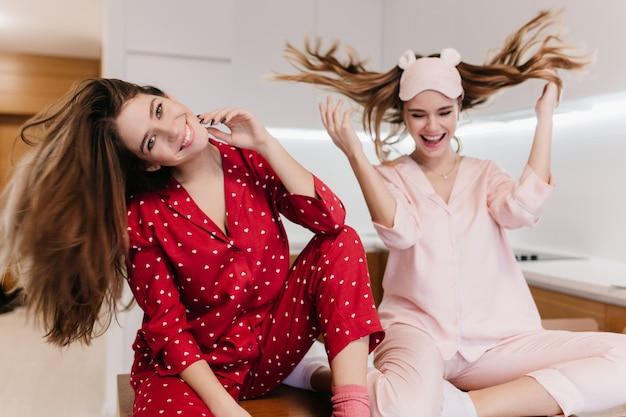 Beztroskie europejskie dziewczyny wyrażające pozytywne emocje podczas pozowania w kuchni. urocze białe modelki w ślicznej piżamie machające włosami i śmiejące się.