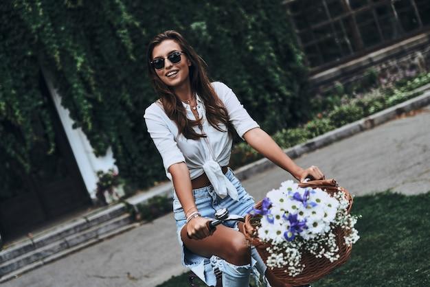 Beztroskie poruszanie się. atrakcyjna młoda kobieta w stroju casual uśmiecha się podczas jazdy na rowerze na świeżym powietrzu