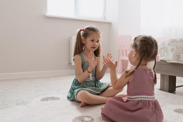 Beztroskie słodkie dziewczyny bawiące się pięknie w domu
