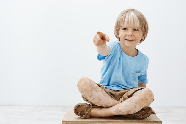 Beztroskie szczęśliwe blond dziecko bawi się, siedzi ze skrzyżowanymi stopami i wskazuje na bok, uśmiechając się szeroko, z zainteresowaniem i ciekawością