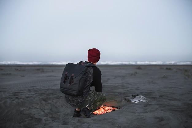 Beztwarzowy mężczyzna blisko ogienia