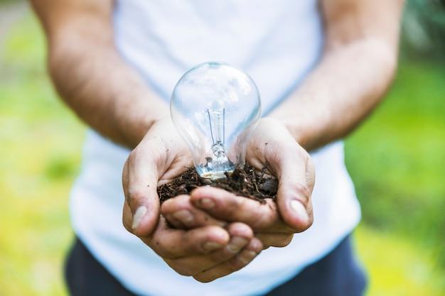 Beztwarzowy mężczyzna trzyma lampę na ziemi