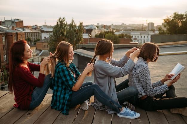 Bff wspiera opiekę przyjaźni. dziewczyny zaplatają sobie nawzajem włosy. koncepcja pracy zespołowej