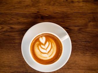 Biała filiżanka na drewno stole, kawowy czas