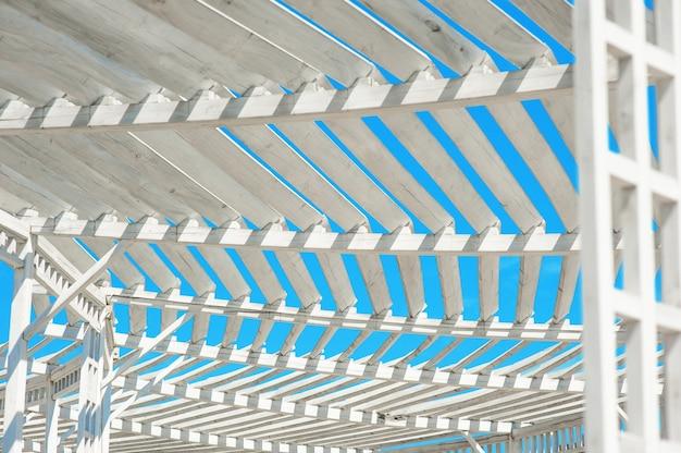 Biała altana w parku przeciw błękitne niebo