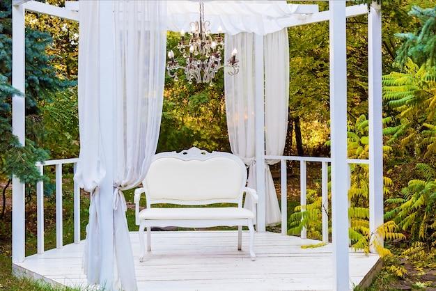 Biała altana z krzesłem i żyrandolemświąteczna strefa fotograficzna na ulicy z meblami