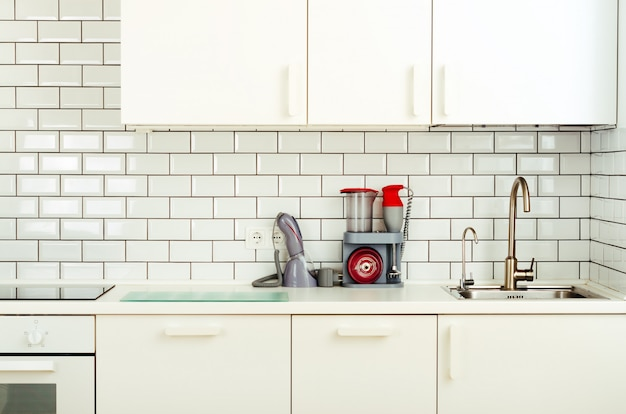 Biała aranżacja wnętrz, nowoczesna i minimalistyczna kuchnia ze sprzętem agd.