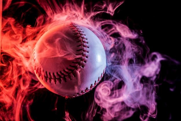 Biała baseball piłka w wielobarwnym czerwień dymu od vape na czarnym odosobnionym tle