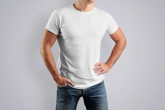 Biała bawełniana koszulka z młodym facetem pozującym na szarej ścianie.