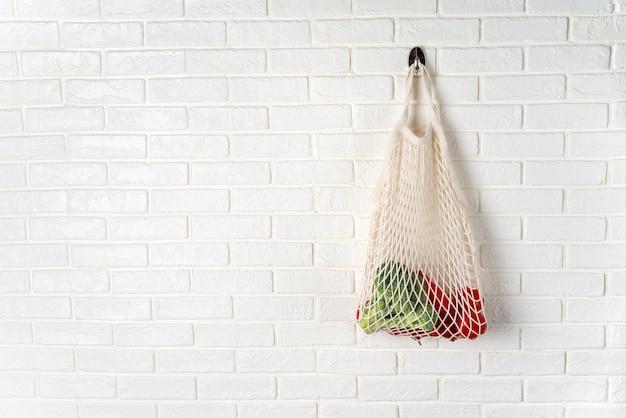 Biała bawełniana siatkowa torba z warzywami wiszącymi na białej ścianie