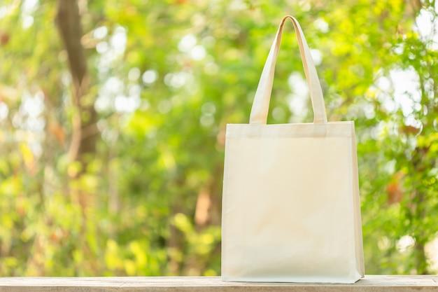 Biała bawełniana torba postawiona na drewnianym stole z miejscem na tekst lub reklamę. bawełnianą torbę można wykorzystać na zakupy, aby zastąpić plastikową torbę na zieleni