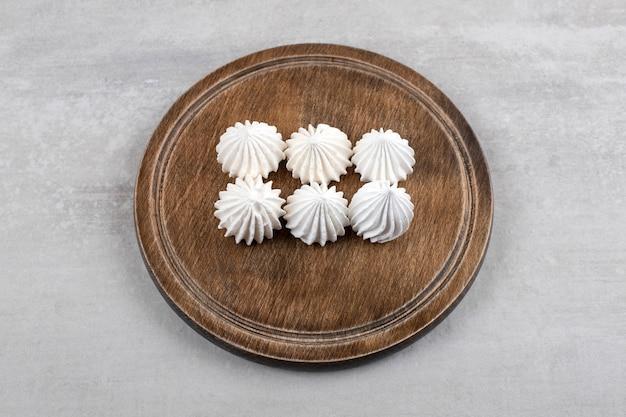 Biała beza na desce, na marmurowym stole.