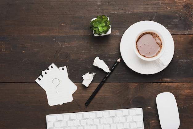 Biała bezprzewodowa klawiatura i filiżanka kawy na drewnianym brązowym stole, widok z góry, miejsce pracy
