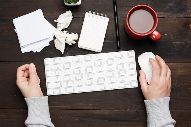 Biała bezprzewodowa klawiatura i mysz na drewnianym brązowym stole, obok białej filiżanki z kawą, widok z góry