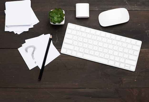 Biała bezprzewodowa klawiatura i mysz na drewnianym brązowym stole, widok z góry, miejsce pracy