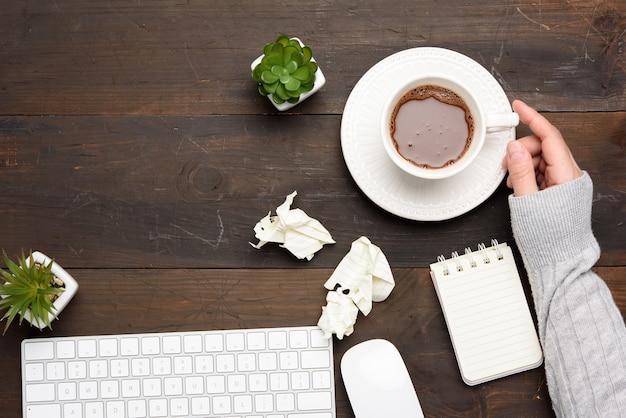 Biała bezprzewodowa klawiatura i mysz na drewnianym brązowym stole