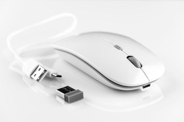 Biała bezprzewodowa mysz komputerowa obok adaptera wi-fi i kabla do ładowania