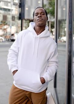 Biała bluza z kapturem na mężczyznę z brązowymi spodniami w mieście