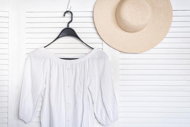 Biała bluzka wisząca na wieszaku. biały drewniany parawan na tle. modna szafa