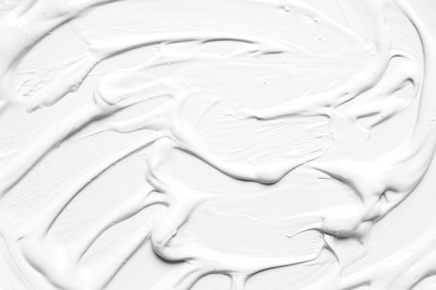Biała błyszcząca farba w niechlujnych ruchach
