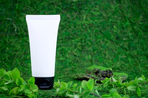 Biała butelka kosmetyczna bez etykiety, na zielonej, naturalnej trawie