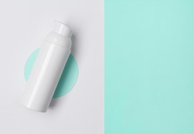 Biała butelka kosmetyczna na minimalistycznym stole z miejsca kopiowania.