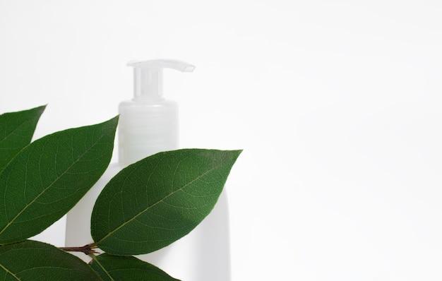 Biała butelka kosmetyczna w liściach na białym tle