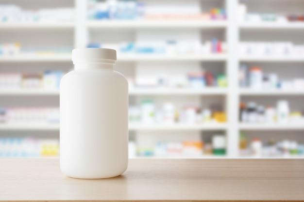 Biała butelka leku na drewnianym blacie z półkami apteki rozmywa tło farmaceutyczne