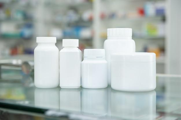 Biała butelka na lekarstwa na ladzie i półce w aptece
