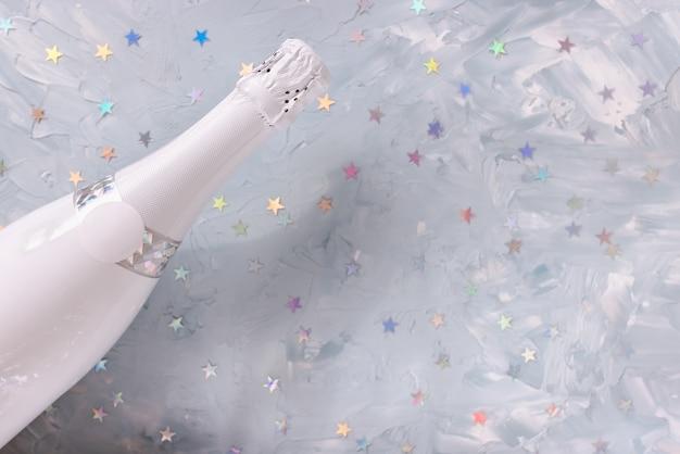 Biała butelka szampana i kolorowe konfetti w metaliczne gwiazdki