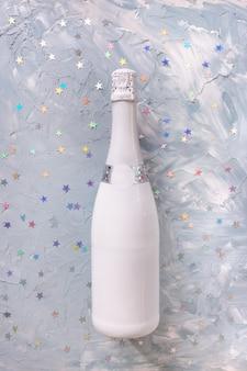 Biała butelka szampana i konfetti koncepcja obchodów nowego roku i bożego narodzenia