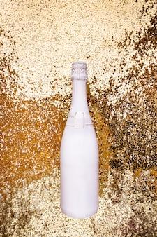 Biała butelka szampana na złotym tle płaski widok z góry modna koncepcja świąteczna
