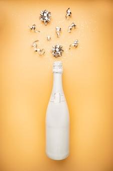 Biała butelka szampana z brokatem i bombkami na pomarańczowym złotym tle płaski widok z góry