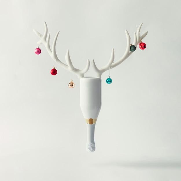Biała butelka szampana z porożem renifera i bombkami bożonarodzeniowymi