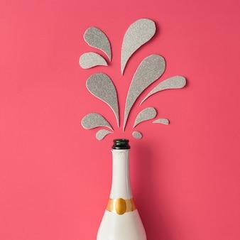 Biała butelka szampana ze srebrnymi błyszczącymi plamami na różowej powierzchni