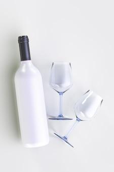 Biała butelka wina i dwie szklanki na jasnej powierzchni.