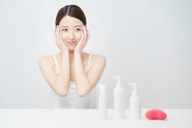 Biała butelka z kobietą, która dotyka twarzy w celu pielęgnacji skóry