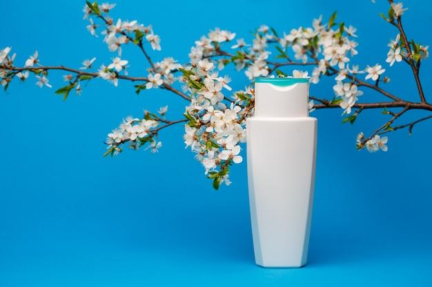 Biała butelka z kremem, szampon do włosów, żel pod prysznic, izolowane niebieskie tło, piękno i młodość ludzkiego ciała, kwitnące drzewo