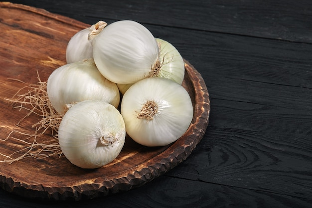 Biała cebula na drewnianej desce na czarnym tle. jedzenie organiczne