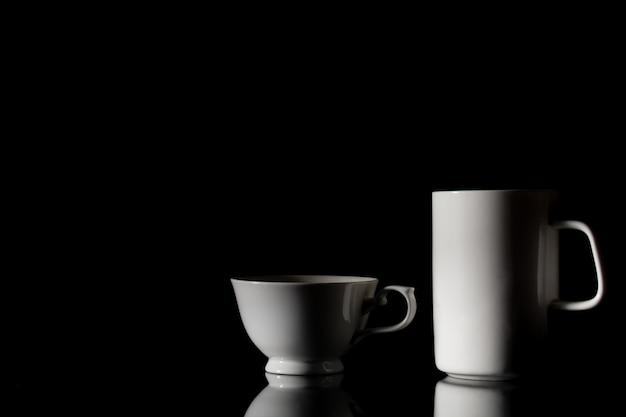 Biała ceramiczna filiżanka do kawy w ciemności.