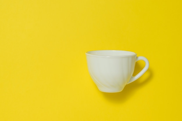Biała ceramiczna filiżanka kawy na żółtym tle. naczynia na gorące napoje.