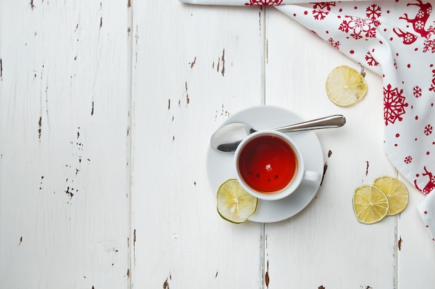 Biała ceramiczna filiżanka z herbatą na spodku świąteczna dekoracja na drewnianym tle