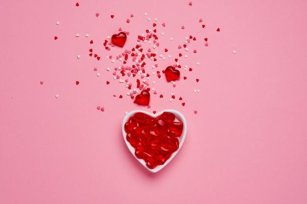 Biała ceramiczna miseczka w kształcie serca z czerwonym konfetti w kształcie serca i małymi ozdobnymi serduszkami na różowym stole. koncepcja walentynki. widok z góry, miejsce na kopię.