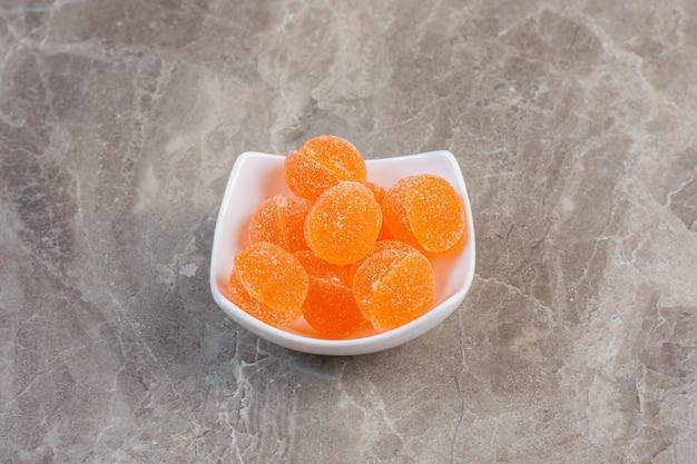 Biała ceramiczna miska pełna pomarańczowej galaretki na szarej powierzchni.