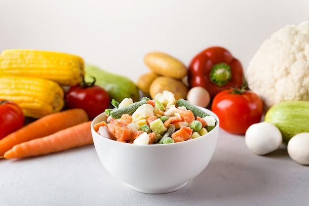 Biała ceramiczna miska z mieszanką mrożonych warzyw z bliska na szarym tle i świeżej żywności