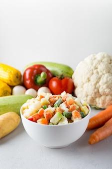 Biała ceramiczna miska z mieszanką mrożonych warzyw z miejscem na tekst na szarym tle i świeżą żywnością