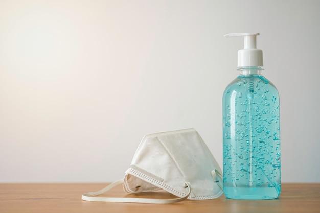 Biała chirurgiczna maska na twarz i alkoholowy żel na drewnianym stole do noszenia w celu ochrony przed covid-19 lub wirusem koronowym, kurzem zanieczyszczającym, bakteriami.