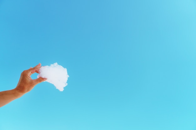 Biała chmura w dłoni na tle błękitnego nieba.