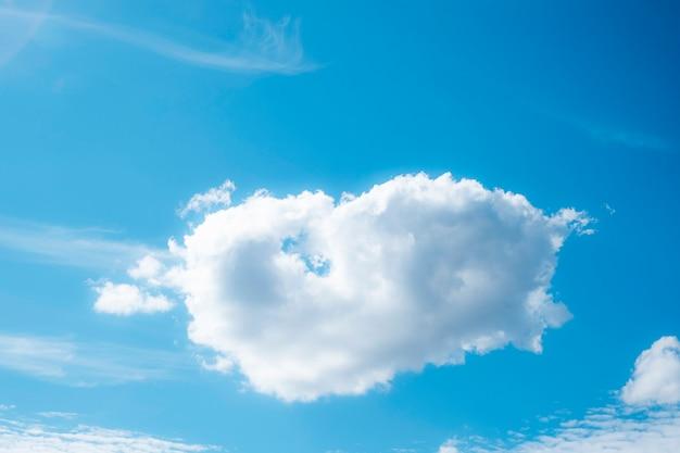 Biała chmura w kształcie serca na niebieskim niebie.