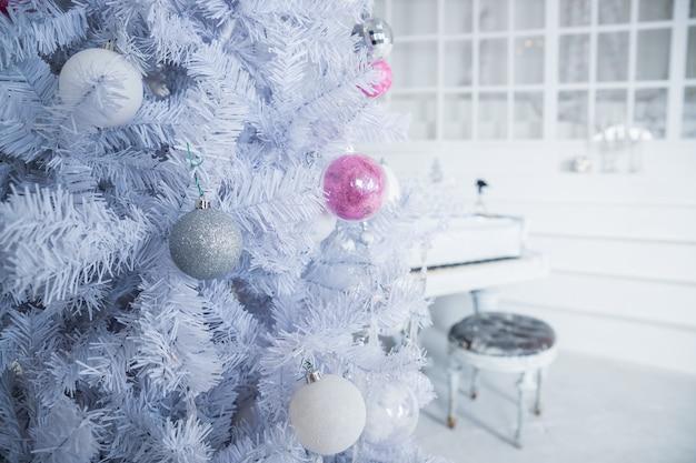 Biała choinka ozdobiona srebrnymi i różowymi zdobieniami przy fortepianie